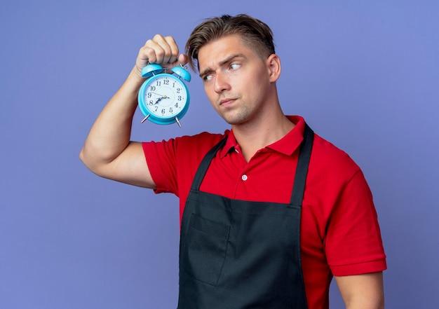 Junger genervter blonder männlicher friseur in uniform hält und betrachtet wecker isoliert auf violettem raum mit kopienraum