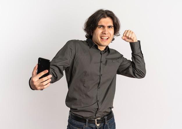 Junger genervter hübscher kaukasischer mann erhebt faust und hält telefon, das kamera lokalisiert auf weißem hintergrund mit kopienraum betrachtet