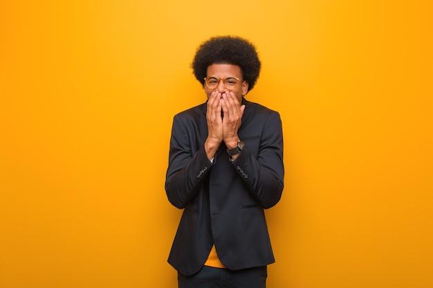 Junger geschäfts-afroamerikanermann auf einer orange wand, die über etwas lacht, mund mit händen kegelnd
