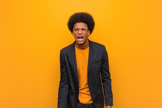 Junger geschäfts-afroamerikanermann über einer orange wand, die sehr wütend und aggressiv schreit
