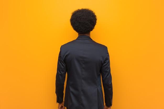 Junger geschäfts-afroamerikanermann über einer orange wand von hinten, zurückblickend