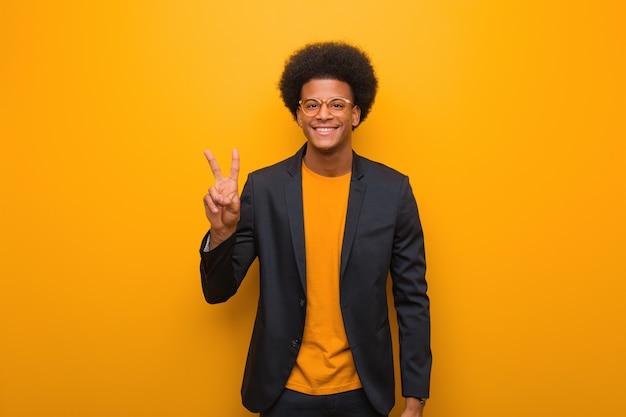 Junger geschäftsafroamerikanermann über einem orange wandspaß und glücklich, eine geste des sieges tuend