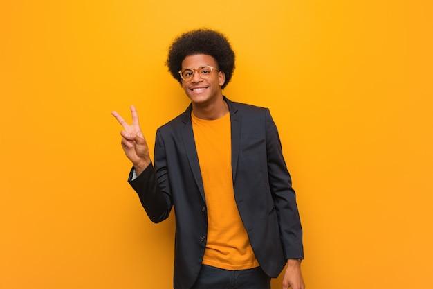 Junger geschäftsafroamerikanermann über einer orange wand, die eine geste des sieges tut