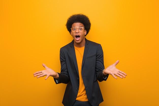 Junger geschäftsafroamerikanermann über einer orange wand, die einen sieg oder einen erfolg feiert