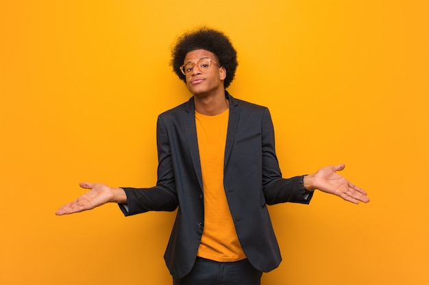 Junger geschäftsafroamerikanermann über einer orange wand, die schultern zweifelt und zuckt