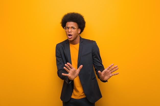 Junger geschäftsafroamerikanermann über einer orange wand etwas zurückweisend, eine geste des ekels tuend