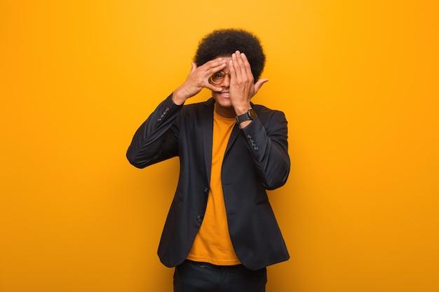 Junger geschäftsafroamerikanermann über einer orange wand fühlt sich besorgt und erschrocken