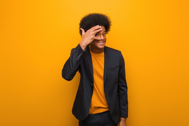Junger geschäftsafroamerikanermann über einer orange wand gleichzeitig verlegen und lachend
