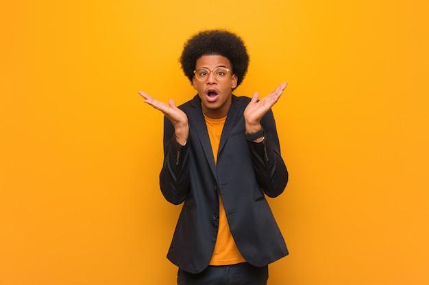 Junger geschäftsafroamerikanermann über einer orange wand überrascht und entsetzt