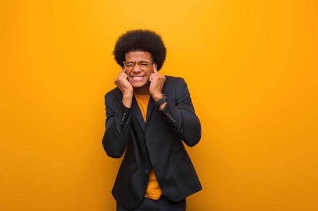 Junger geschäftsafroamerikanermann über ohren einer orange wandverkleidung mit den händen
