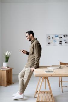 Junger geschäftsangestellter in der freizeitkleidung, die im smartphone beim stehen durch tisch vor bürofenster rollt