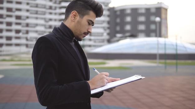 Junger geschäftsinhaber, der über neue produktideen mit stift- und papierordner nachdenkt.