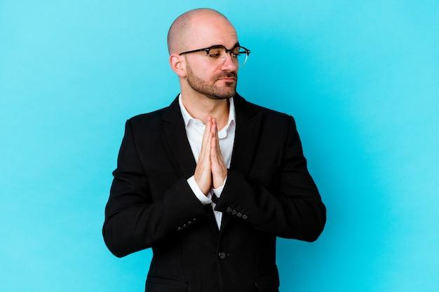 Junger geschäftskahlköpfiger mann lokalisiert auf blauer wand betend, zeigt hingabe, religiöse person, die nach göttlicher inspiration sucht