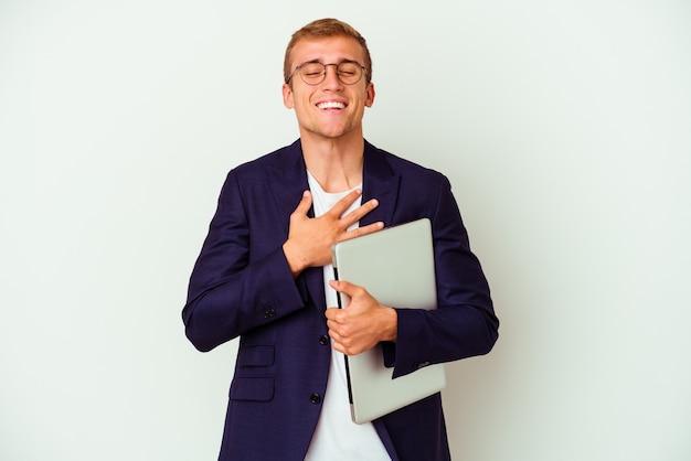 Junger geschäftskaukasier, der einen laptop hält, der auf weißer wand lokalisiert wird, lacht laut und hält hand auf brust.