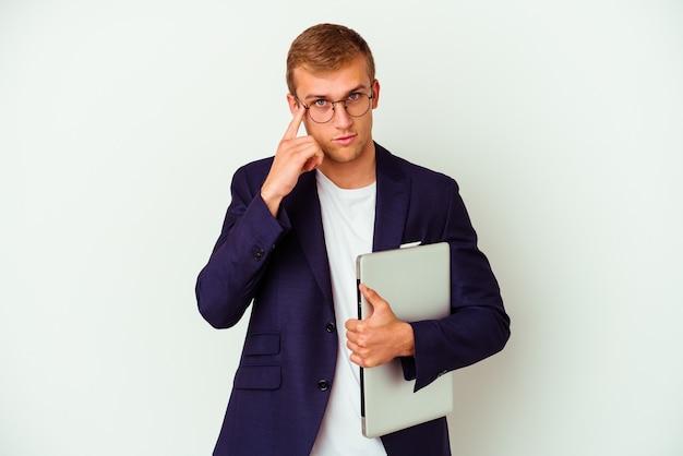 Junger geschäftskaukasiermann, der einen laptop lokalisiert auf weißer wand zeigt tempel mit finger, denkend, fokussiert auf eine aufgabe.