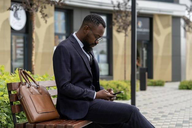 Junger geschäftsmann afrikanischer abstammung sms im smartphone beim ausruhen auf der bank