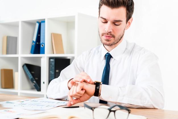 Junger geschäftsmann am arbeitsplatz die zeit auf armbanduhr aufpassend