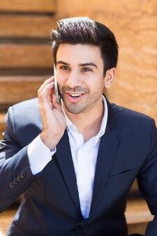 Junger geschäftsmann am telefon zu sprechen lächelnd