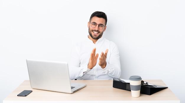 Junger geschäftsmann an einem arbeitsplatz applaudierend nach darstellung in einer konferenz