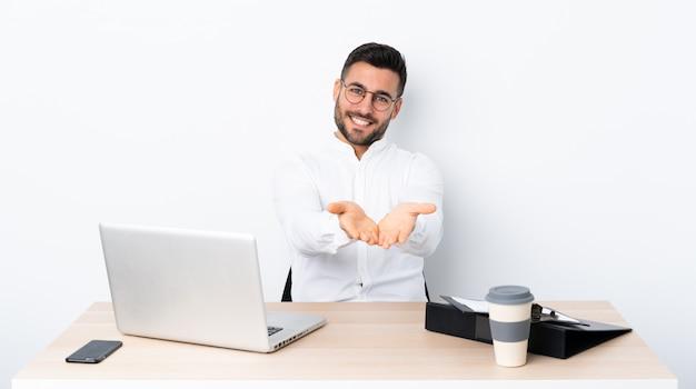 Junger geschäftsmann an einem arbeitsplatz, der copyspace eingebildet auf der palme hält, um eine anzeige einzufügen