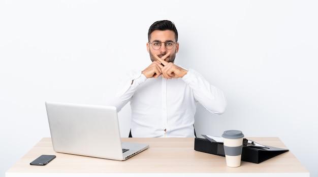 Junger geschäftsmann an einem arbeitsplatz, der ein zeichen der ruhegeste zeigt