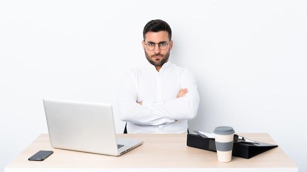Junger geschäftsmann an einem arbeitsplatz, der gestört glaubt