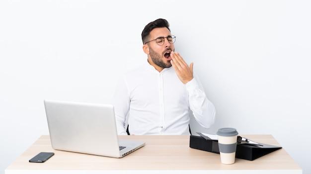 Junger geschäftsmann an einem arbeitsplatz, der weit offenen mund mit der hand gähnt und bedeckt