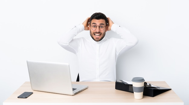 Junger geschäftsmann an einem arbeitsplatz frustriert und nimmt hände auf kopf