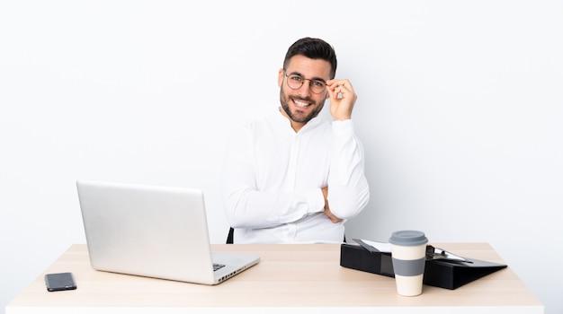 Junger geschäftsmann an einem arbeitsplatz mit gläsern und glücklich