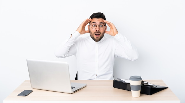Junger geschäftsmann an einem arbeitsplatz mit überraschungsausdruck