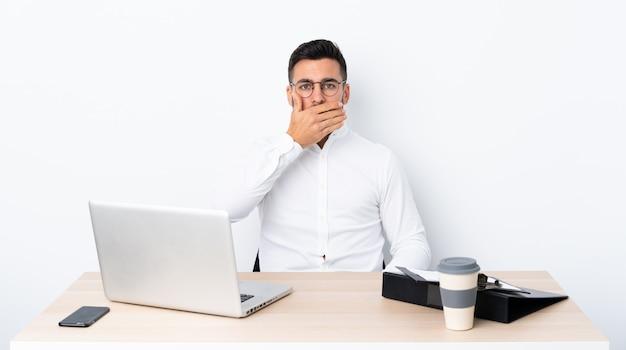 Junger geschäftsmann an einem arbeitsplatzbedeckungsmund mit den händen