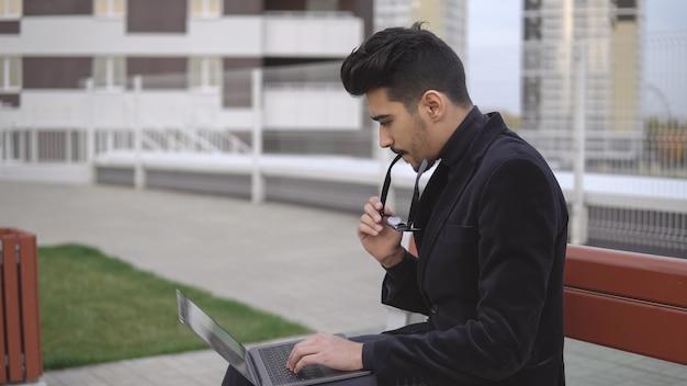 Junger geschäftsmann arbeitet seit langem am tablet-computer und ist müde im freien