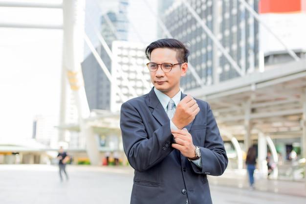 Junger geschäftsmann asiens vor dem modernen gebäude herein in die stadt