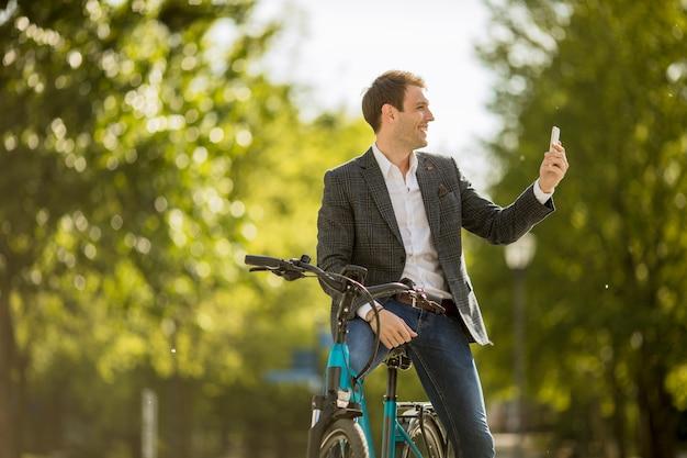 Junger geschäftsmann auf dem e-bike, der handy verwendet, um selfie-foto zu machen