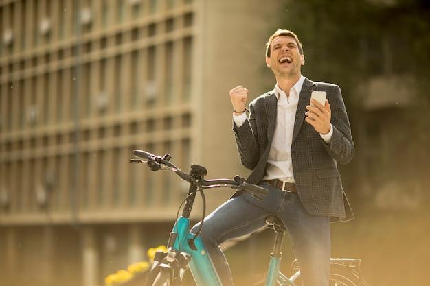 Junger geschäftsmann auf dem e-bike erhielt große neuigkeiten per handy