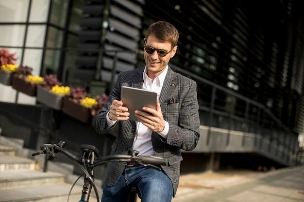 Junger geschäftsmann auf dem e-bike mit digitalem tablett