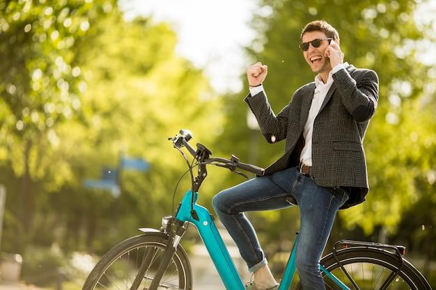 Junger geschäftsmann auf dem e-bike mit handy