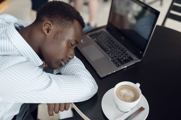 Junger geschäftsmann aus ebenholz mit laptop, der im bürocafé schläft. müde geschäftsmann trinkt kaffee im food-court, schwarzer mann in abendgarderobe