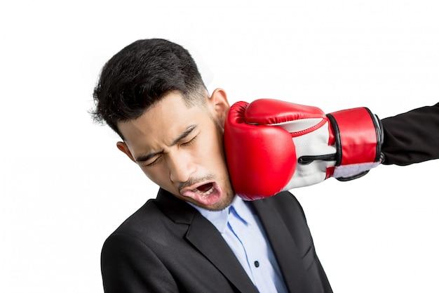 Junger geschäftsmann bekommt schlag in sein gesicht mit roten boxhandschuhen. geschäftswettbewerbskonzept