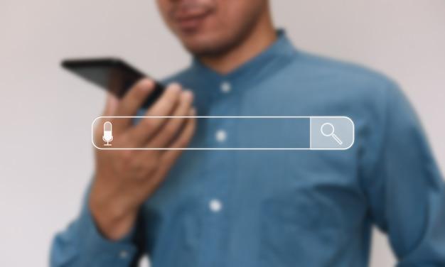 Junger geschäftsmann benutzt smartphone im haus. aufzeichnen von audiosuchdaten im internet