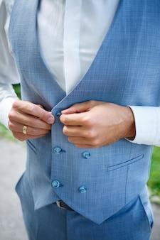 Junger geschäftsmann bräutigam an ihrem hochzeitstag, stilvolle kleidung, ein spaziergang im park