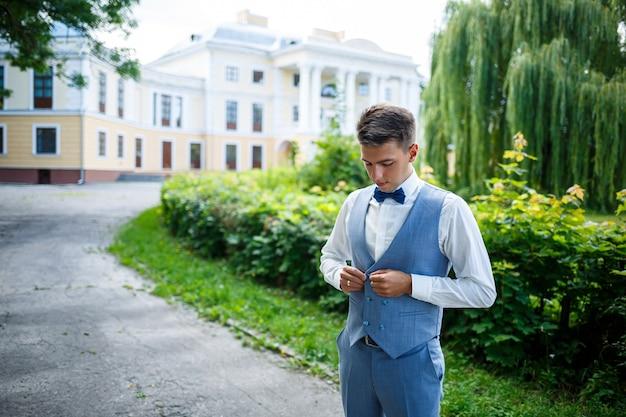 Junger geschäftsmann bräutigam an ihrem hochzeitstag, stilvolle kleidung, ein spaziergang im park Premium Fotos