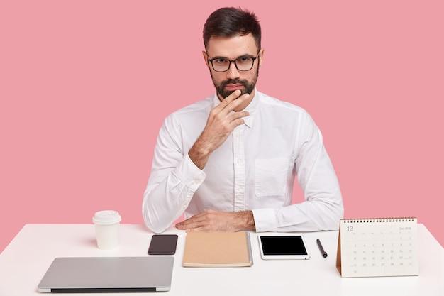 Junger geschäftsmann, der am schreibtisch mit gadgets sitzt
