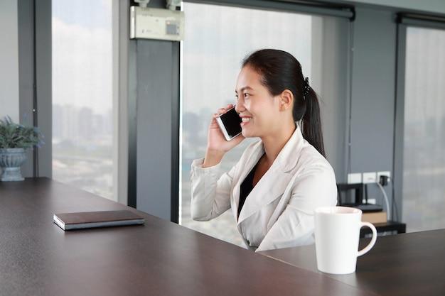 Junger geschäftsmann, der am stuhl auf arbeitsplatz im büro spricht mit telefon sitzt.