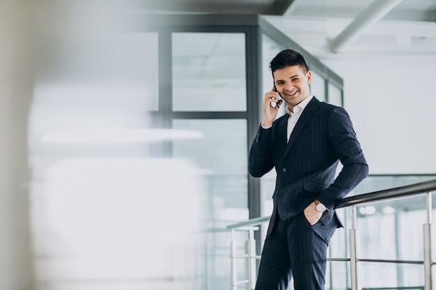 Junger geschäftsmann, der am telefon im büro spricht