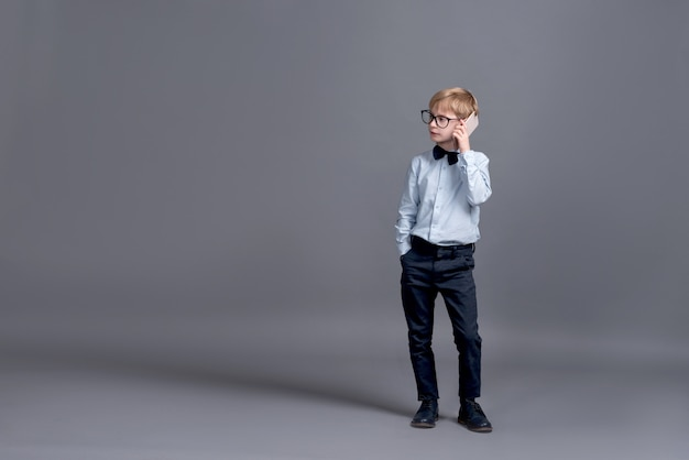 Junger geschäftsmann, der am telefon spricht. kleiner junge, der auf einem grau aufwirft