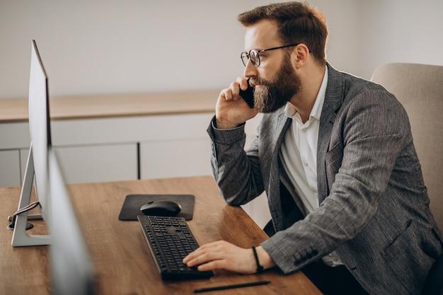 Junger geschäftsmann, der am telefon spricht und am computer arbeitet