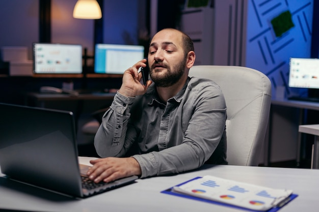 Junger geschäftsmann, der am telefon spricht und einen laptop an seinem schreibtisch verwendet. manager, der ein geschäftsgespräch mit smartphone führt, während er überstunden im büro macht.