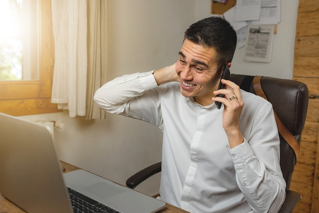 Junger geschäftsmann, der am telefon spricht und sich schuldig fühlt, besorgt für ein problem bei der arbeit, legte hand hinter kopf.