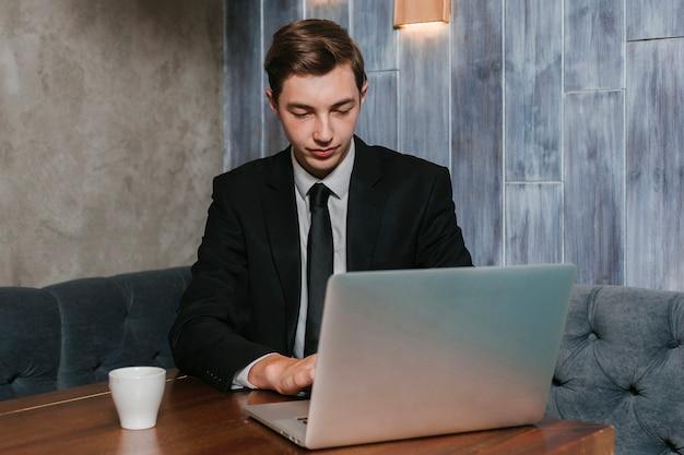 Junger geschäftsmann, der an dem laptop arbeitet